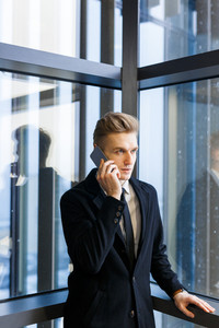 Concentrated young entrepreneur in stylish suit talking to his client on smartphone while standing by panoramic window, portrait shot