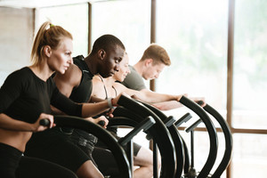 Concentrated young people working out on treadmills at the gym