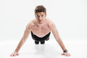 Concentrated young sportsman doing push-ups isolated over white