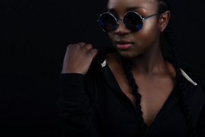 Confident african woman with dark skin wearing round sunglasses