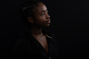 Confident and happy Black Female Model Looking Away Against Black Background