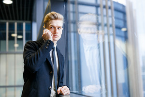 Confident blond-haired office worker phoning to his client while standing by window of office lobby and looking away, waist-up portrait