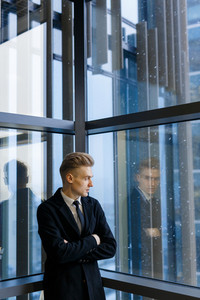 Confident businessman standing with arms crossed in office lobby and looking out panoramic window, waist-up portrait