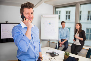 Confident Businessman Using Smart Phone In Office