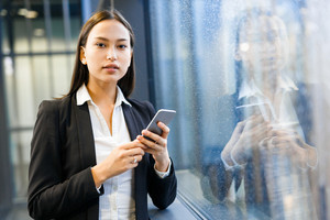 Confident businesswoman with smartphone looking at camera