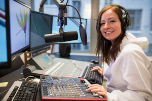 Confident Female Host Smiling In Radio Station