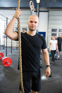 Confident Male Athlete Holding Gym Rope In Health Club