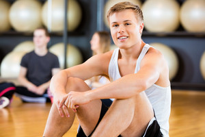 Confident Man Sitting In Fitness Studio