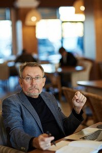 Confident mature man in eyeglasses looking at camera seriously while sitting on comfortable cafe armchair and preparing business presentation on laptop, waist-up portrait