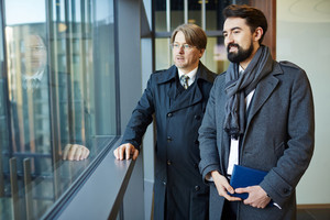 Confident middle-aged businessmen wearing coats standing in office lobby and looking out panoramic window, portrait shot