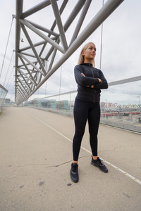 Confident Woman in Black Workout Wear Standing At Modern Bridge In City