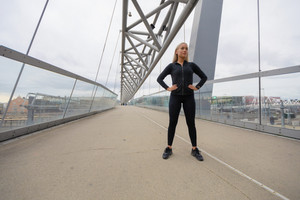 Confident Woman with Hands on the Hips in Workout Outfit Standing on Bridge