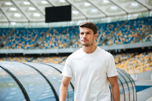 Confident young sportsman walking at the stadium