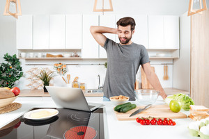 Confused handsome man cooking vegetable salad in kitchen with laptop