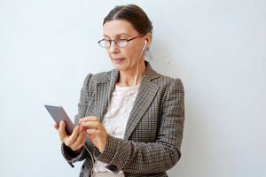 Contemporary businesswoman watching something online in her smartphone
