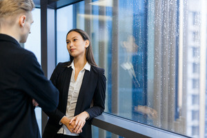 Conversation of young managers by office window