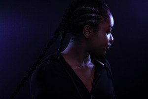 Cool and Beautiful Black Female Model Looking Away In Purple Light