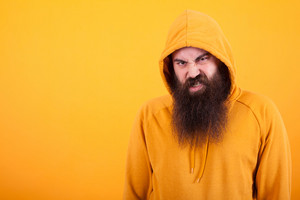 Cool bearded hipster looking at the camera with angry face over yellow background. Trendy man. Stylish man.