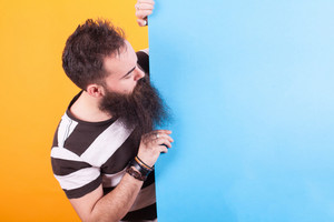 Cool bearded man looking at blue copy space over yellow background. Cool t-shirt. Men style.