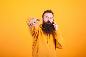 Cool bearded man looking at the camera and talking on the phone over yellow background. Handsome man. Confident man.