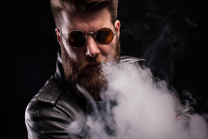 Cool bearded man looking at the camera wearing leather jacket over black background. Attractive stylish man.
