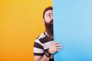 Cool bearded man looking up behind a blue panel over yellow background. Facial expression. Stylish man. Great beard.