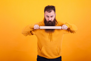 Cool bearded man using kitchen paddle and looking at the camera over yellow background. Kitchen equipement.