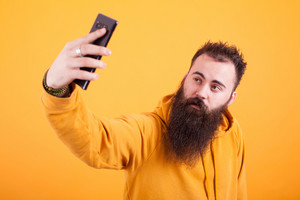 Cool Bearded man wearing yellow hoodie and taking selfie over yellow background. Hipster man. Stylysh man,