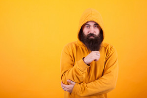 Cool Hipster playing with his long beard and looking at the camera over yellow background. Handsome man. Stylish man. Cool beard.