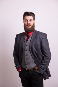 Cool young bearded man in grey business suit looking at the camera over white background. Long beard. Stylish beard.