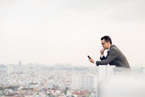 Copy-spaced image of a businessman making a telephone call while standing on the roof