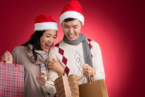 Copy-spaced image of a young amazing couple with paperbags full of presents over a red background