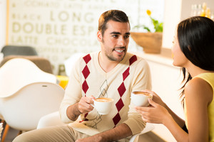 Copy-spaced image of a young man talking with his girlfriend at a cafe over a coffee on the foreground