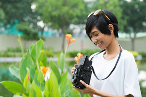 Copy-spaced image of a young woman with a retro camera outside