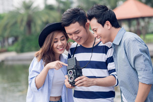 Copy-spaced image of happy friends having fun with vintage photo camera outside