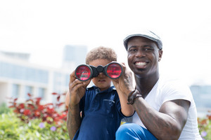 Copy-spaced portrait of a father and his son with binoculars in the park