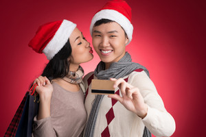 Copy-spaced shot of a young happy couple after x-mas shopping against a red background