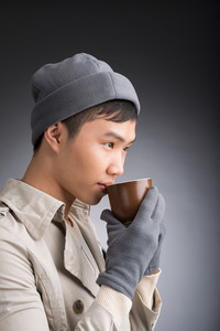 Copy-spaced shot of a young man drinking hot coffee over a grey background