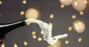 Cork flying off a bottle of sparkling wine on festive gray background with lights and lens flare. slowmotion
