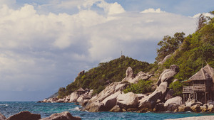 Costline of Koh Tao Islands in Thailand. Granite Rocks and blue clear water hitting Rocks