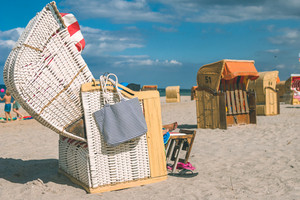 Couple chill relax in striped roofed chairs on sandy beach in Travemunde. , Lubeck, Germany