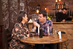 Couple drinking red wine and sharing a beautiful moment in a hipster pub. Joy time.