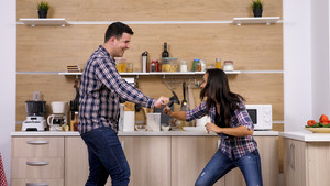 Couple having a duel in their kitchen while dinner is ready,. Fight time.