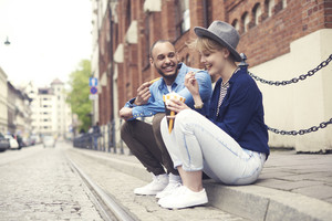 Couple having fast food sitting on the sidewalk