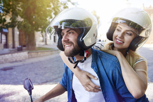 Couple in helmets riding a scooter