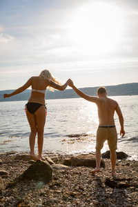 Couple in love holding hands at the beach against sun