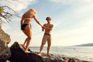 Couple in love holding hands at the beach at summer
