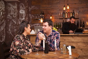 Couple on a date sitting in a hipster pub drinking red wine. Celebration .