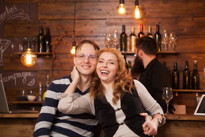 Couple On Date Sitting At Bar Counter And smiling. Hipster pub.