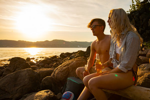 Couple relaxing and drinking beer at the beach at sunset
